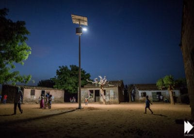 A street-lamp lit by night in the middle of a village in Senegal